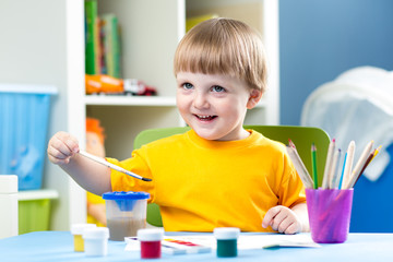 baby boy painting at table in children room