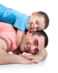 Happy kid boy and his dad lying on the floor