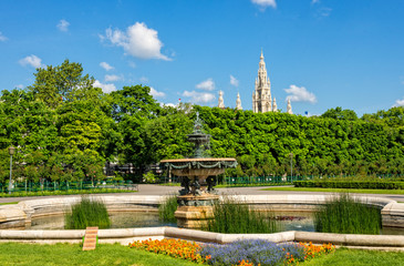 Fountain and pond in Volksgarten with Rathaus in background