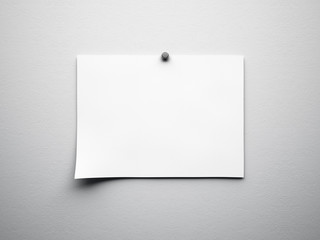 piece of blank paper tacked to white wall
