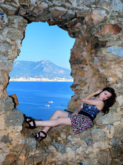 Girl lying on a stone wall near the sea