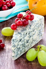 Blue cheese with fruits on wooden background