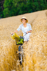 Woman rides cycle with apples and flowers in rye field.