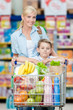 Mother and son with cart full of products in store