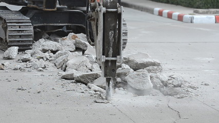 Excavator breaking concrete road surface.