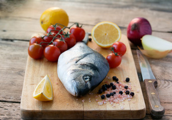 fresh gilt-head bream fish on cutting board