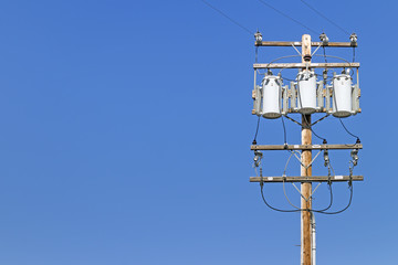 Electric utility pole with 3 transformers.Blue sky background.