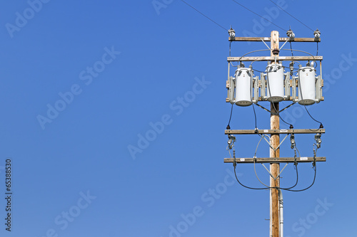 canvas print picture Electric utility pole with 3 transformers.Blue sky background.
