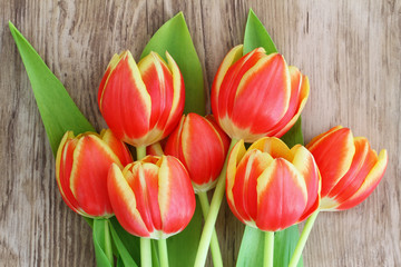 Red and yellow tulips on wooden surface