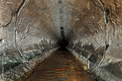 Fotobehang Rudnes Deep sewage tunnel with poinson flowing