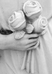 bouquet of roses in hand - detail of cemetery  angelic sculpture