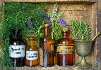 Apothekerfläschchen und frische Kräuter in altem Holzregal