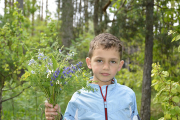 Boy standing in the woods with a bouquet of flowers.