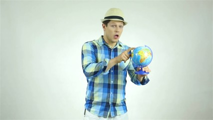 Handsome man holding a globe and pointing place