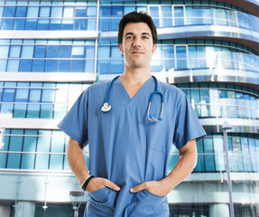 Medical worker in front of a modern hospital