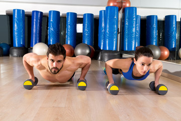 Dumbbells push-ups couple at fitness gym