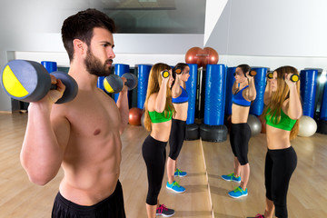 Dumbbell weightlifting man women group at mirror