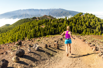 Young woman trail running in mountains on sunny summer day