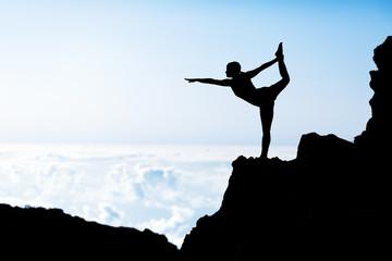 Woman doing yoga sunset silhouette