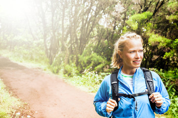 Woman hiker or trail runner in green forest