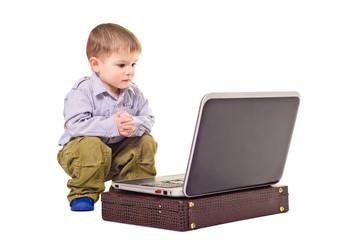 Cute little boy sitting near a laptop