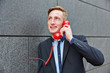 Geschäftsmann redet am roten Telefon