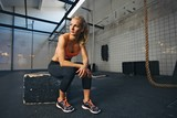 Fototapety Female athlete taking rest after exercising at gym
