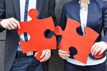 Geschäftsleute halten zwei große Puzzleteile