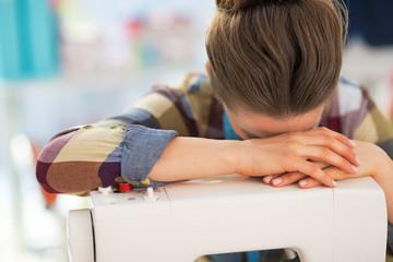Stressed seamstress near sewing machine