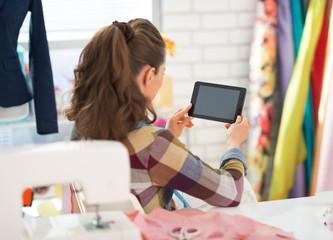 Seamstress using tablet pc at work. rear view
