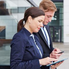 Geschäftsleute arbeiten mit Tablet Computer und Smartphone