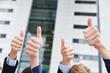 Geschäftsleute halten Daumen hoch vor Büro