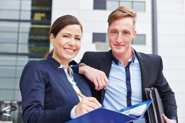 Zwei Anwälte lächeln vor dem Büro