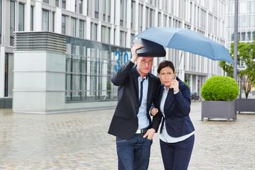 Geschäftsleute unter Regenschirm im Regen