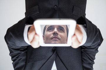 Upside down businessman with digital tablet