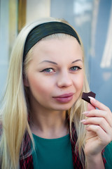 Beautiful blond girl eating chocolate