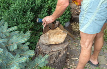 A wooden block with the axes that were stuck in it and hand of t