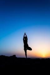 Woman doing yoga tree pose sunset silhouette