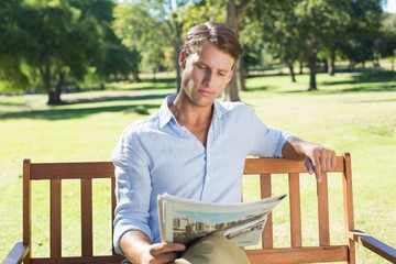 Handsome man sitting on park bench reading newspaper