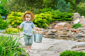 Cute country style kid posing with bucket and rod