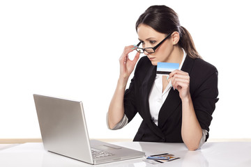 focused woman holding credit card and looking at her laptop