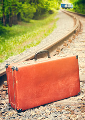vintage suitcase on the railway, blue train is off