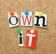 The phrase Own It in magazine letters on a cork notice board - 65409956