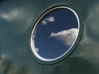 Reflejo de cielo sobre ventana circular, ojo de buey