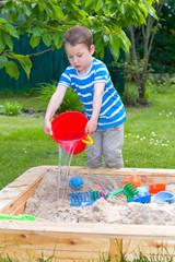 kleiner Junge mit Wassereimer im Sandkasten