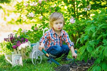 Little kid helping in the garden with proper utensils