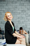Young happy woman sitting on the table in office