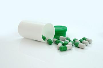 Green pills an pill bottle on white background