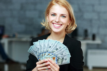 Happy smiling businesswoman holding bills of dollars in office