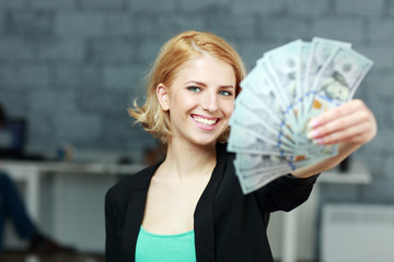 Young happy businesswoman holding bills of dollars in office